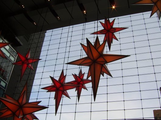 Cascading stars float against the blue sky of the atrium's glass wall setting the holiday spirit of giving and joy. Cricketdiane Walkabout New York City 2010.
